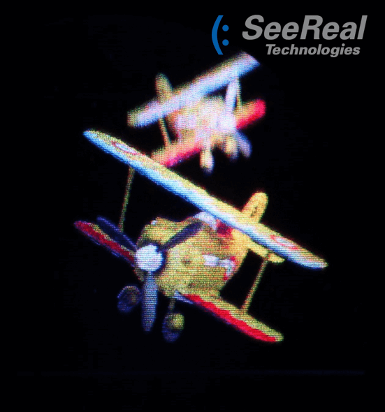 Photography of a real-time holographic 3D scene reconstructed on a SeeReal prototype display - see how focus of reconstructed scene changes when camera focus is switched between foreground and background airplane.